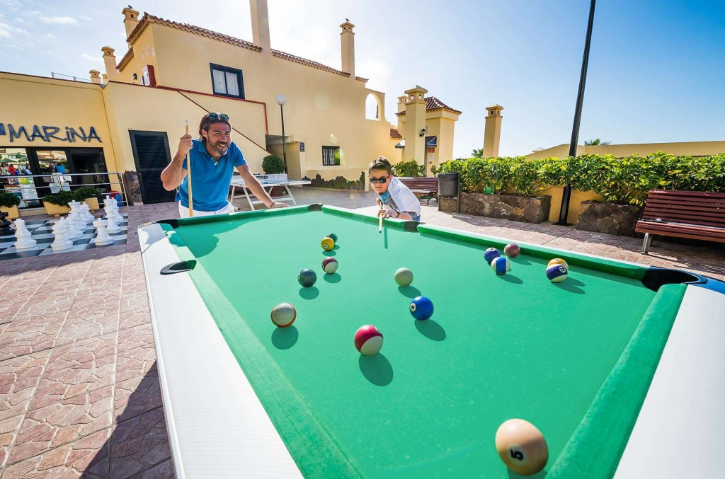 Families have fun playing on the outdoor pool table at Paradise
