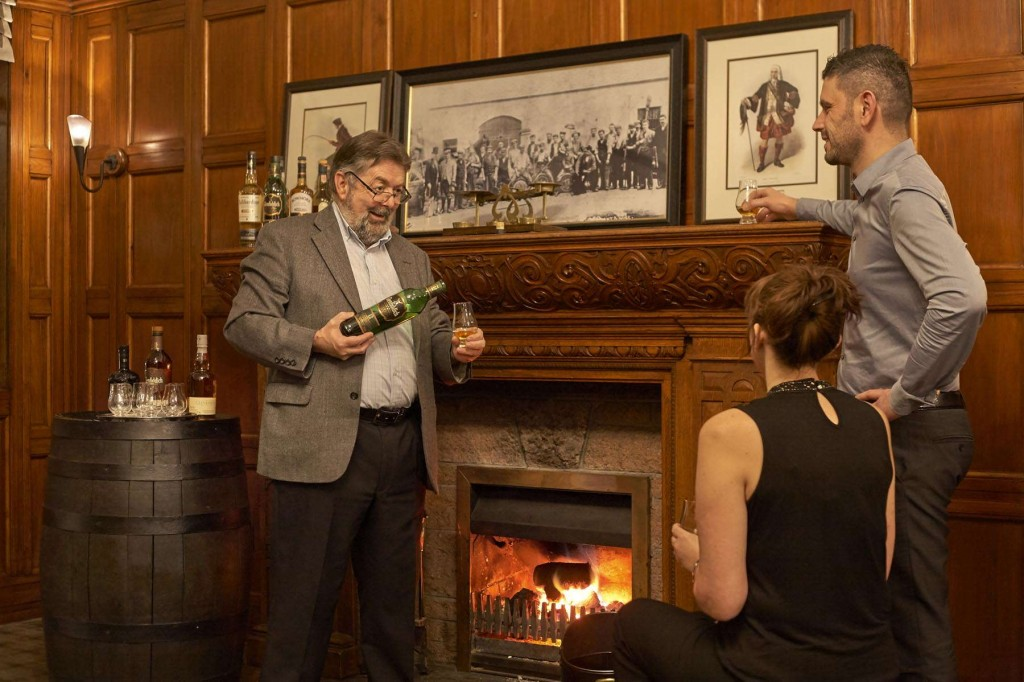Guests relaxing and having a drink by the fireplace at Duchally Country Estate